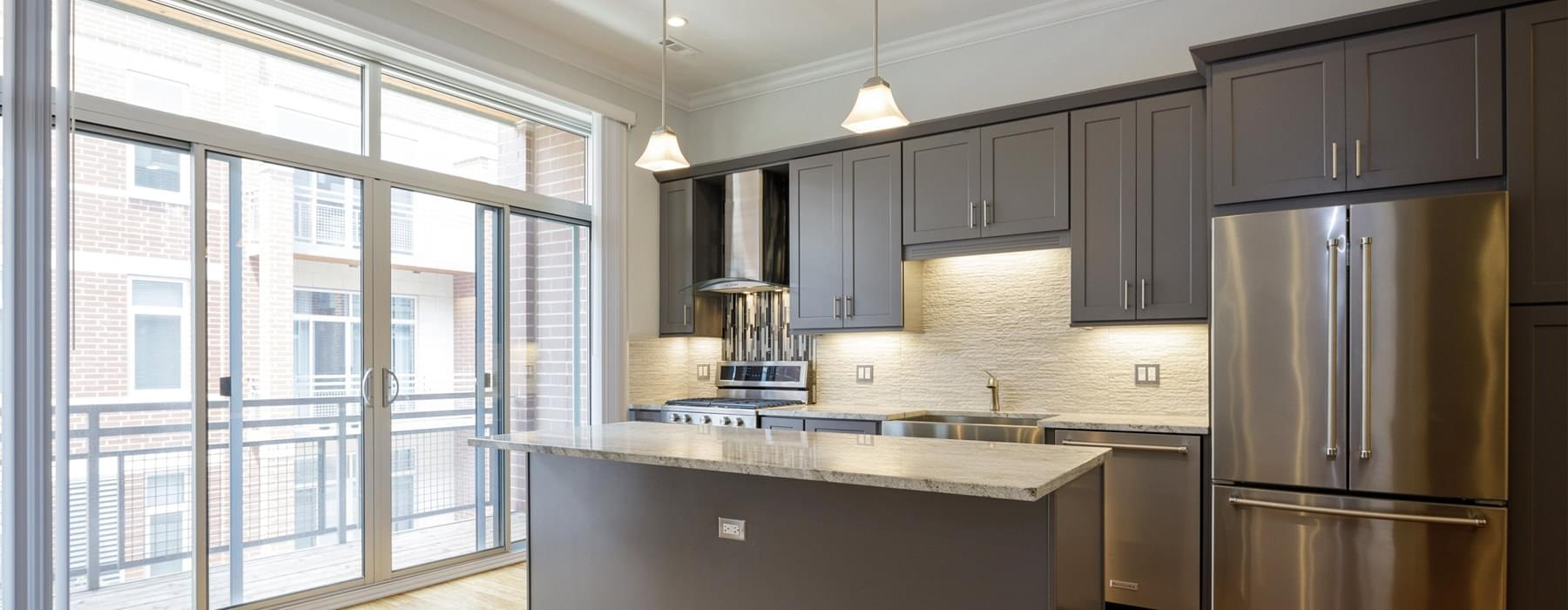 spacious kitchen area brightly lit by glass windows and overhead fixtures